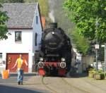 Oleftalbahn/136079/52-6106-mit-dem-ostersonderzug-am 52 6106 mit dem Ostersonderzug am 24.4.2011 bei Durchquerung des Dorfplatzes von Olef. Auf der Oleftalbahn zwischen Kall und Hellenthal ist dies einmalig in ganz Deutschland!
